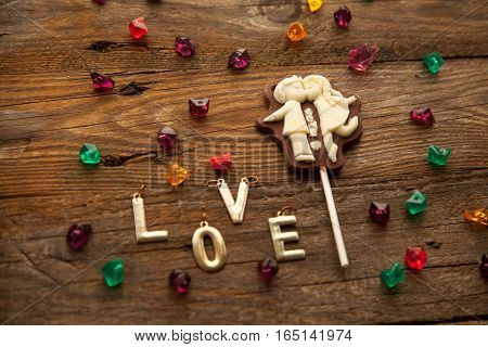 Valentine's day chocolate candy with kissing couple and letters on wooden background.