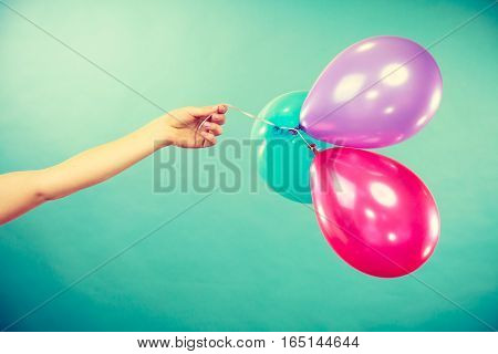Female Hand Holding Colorful Balloons