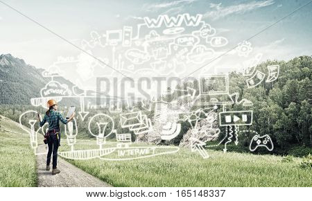 Back view of engineer woman in hardhat outdoor and sketched concept on screen