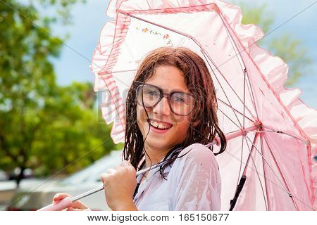 A really wet girl holds a pink frilly umbrella and smiles at the camera. She is wearing large glasses with water drops on them. She has crooked teeth.
