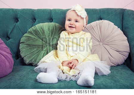 Beautiful blonde small girl with yellow dress and flower on her head sitting on green sofa looking at camera.