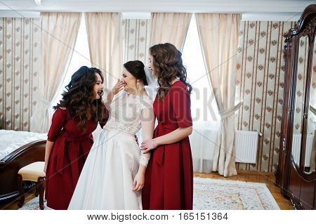 Bride With Two Amazing Bridesmaids On Red Dress Posed On Room At Wedding Day.