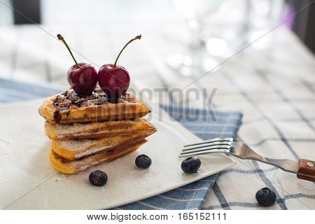 Belgian waffles with berries cake with raspberry and cherry pie on the table