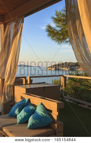 Summertime relax.The most beautiful coasts of Italy: bay of Vieste.-(Apulia, Gargano) -In the foreground the Gattarella or Portonuovo Islet and in the background the town of Vieste.Seascape at sunset sitting on a couch.