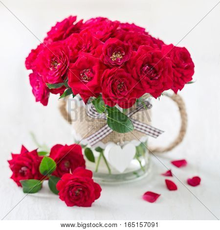 Beautiful red roses .Lovely bunch of flowers .Beautiful fresh roses in a vase decorated with a heart .