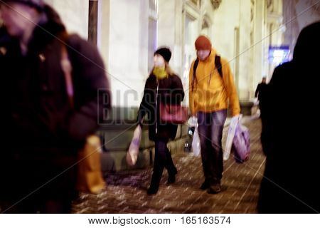 Blurred background. Blurred people walking through city street. winter night
