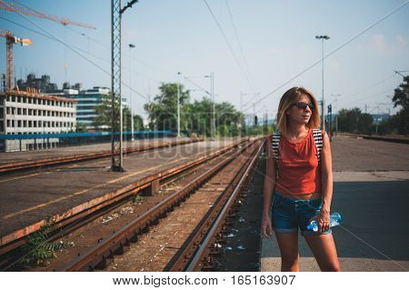 Young female backpacker waiting for the train