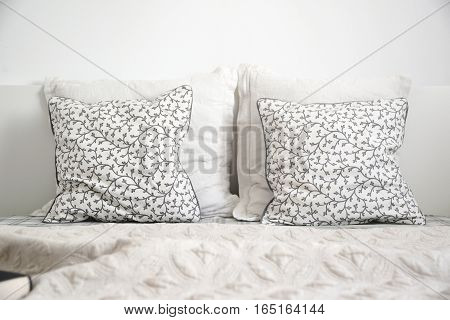 White bedroom detail. Two cushions on a bed. Empty copy space for editor text.