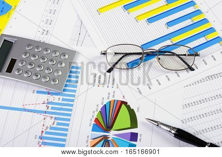 Checking Business Reports. Glasses And Pile Of Documents. Many Graphs And Charts. Pile Of Documents