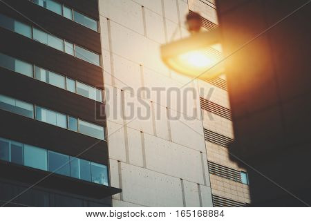 Concrete tiled facade of modern office building in Barcelona with working lantern on a nearby building vintage color filter Forum district Spain