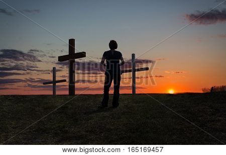 horizontal image of  a silhouette of a lady standing by three crosses on a hill with a beautiful sunset in the background in the summertime