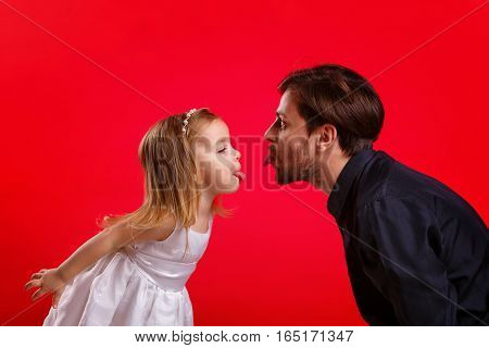 Father and daughter show tongues. Emotional games with your child. Family fun. The joy of communication.