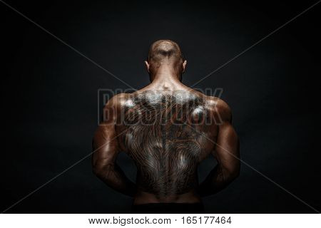 Unrecognizable muscular man with tattoo on back against of black background. Isolated.