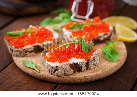 Sandwich with red caviar on wooden table