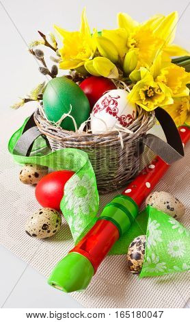 Traditional Czech easter decoration - my handmade painted eggs with daffodils flower quail eggs green ribbon and wooden music instrument flute. Spring easter holiday arrangement.