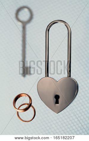 wedding rings steel lock and key on light background