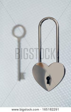steel lock and key on light background