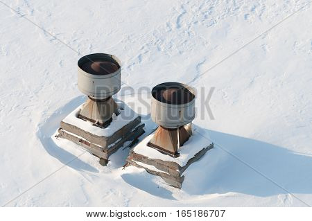 Vent pipes on the roof. The flat roof is completely covered with snow.