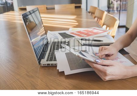 Business office concept. Woman's hands using tablet with financial document in meeting room.