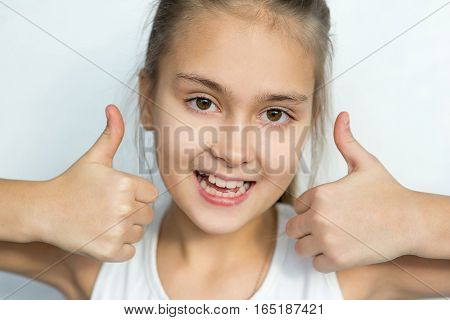 Portrait of young teenager girl emotional posing on white background isolated. thumb up