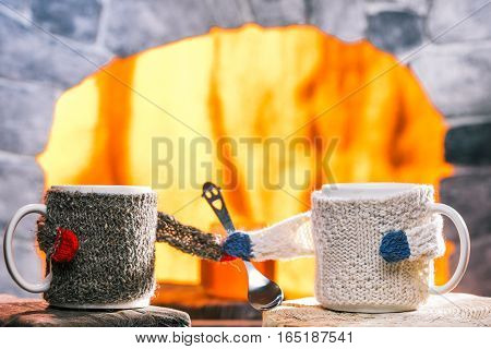 Tea mugs in sweater cozies holding smiling teaspoon. Hearth on the background