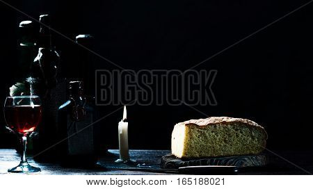Bread loaf next to sealed wine bottles, glass and burning candle in twilight cellar