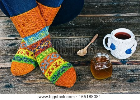 Human feet in colorful winter socks on the floor with tea cup and honey jar. Closeup view