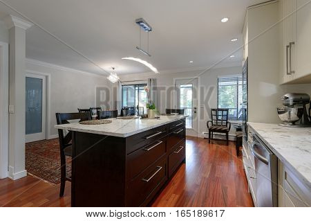 Modern kitchen and dining room interior with stainless steel appliances in a luxury house.