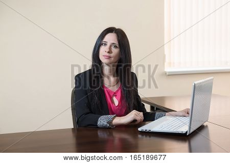 Young attractive woman in a business suit sitting at Desk with laptop in office