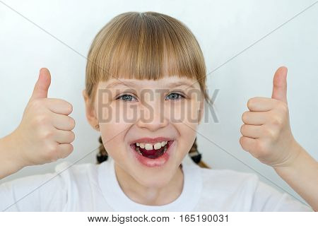 Portrait of young teenager girl emotional posing on white background isolated. Thumbs up