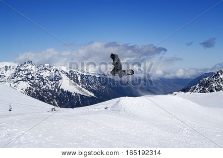 Snowboarder Jumping In Snow Mountains At Sun Winter Day