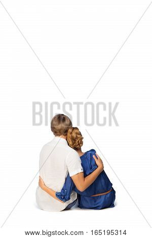 Beautiful couple sitting on floor. Young man and woman. Isolated. Copy space.