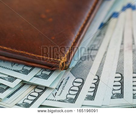 Brown leather wallet with USA dollars money inside it