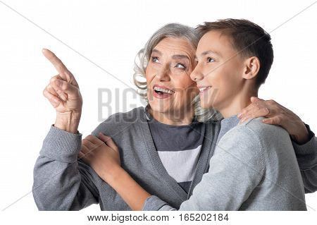 Portrait of grandmother showing something to grandson isolated on white background