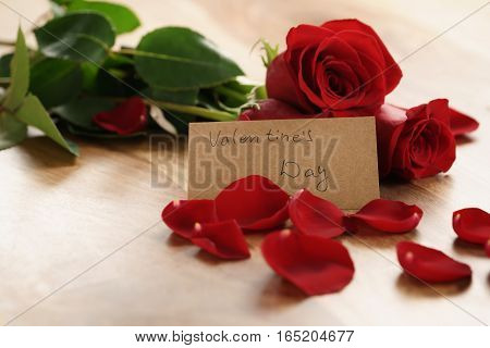 three red roses with petals on wood table and paper card for valentines day, shallow focus