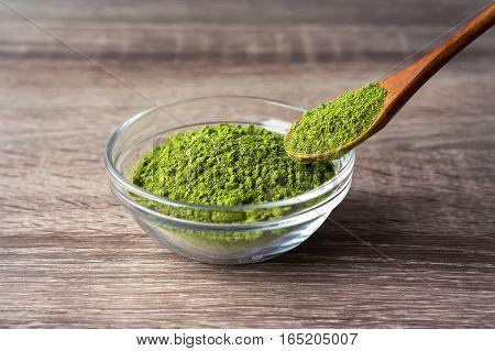 Green matcha tea on a wooden spoon