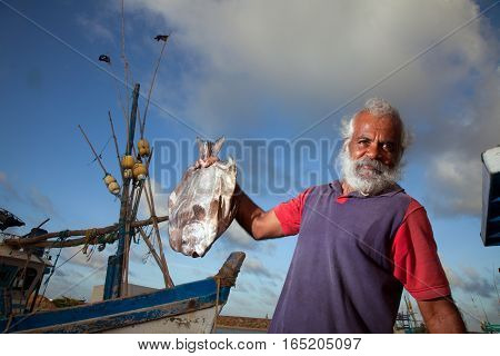The man in the maritime market shows a big fish rejoicing luck