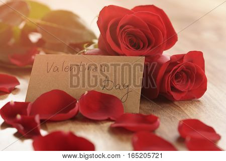 warm photo of three red roses with petals on wood table and paper card for valentines day, shallow focus