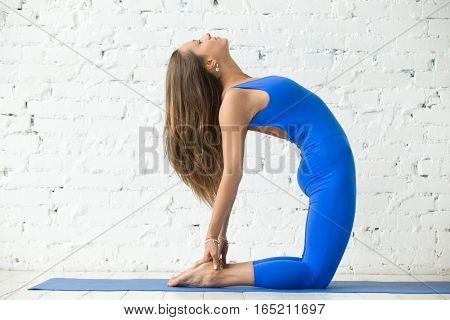 Young attractive happy woman practicing yoga, stretching in Camel exercise, Ustrasana pose, working out, wearing sportswear, blue suit, indoor full length, white loft studio background