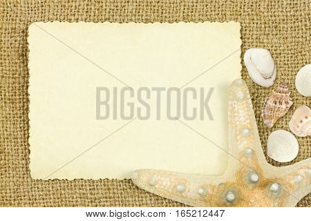 Reverse side of an old photo print with a decorative border sea star and sea sheels on sack cloth background