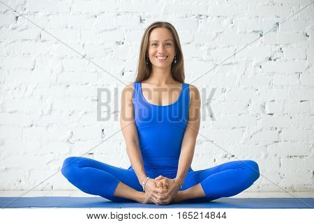 Young attractive woman practicing yoga, sitting in Butterfly exercise, baddha konasana pose, working out, wearing sportswear, blue suit, indoor full length, white loft studio background