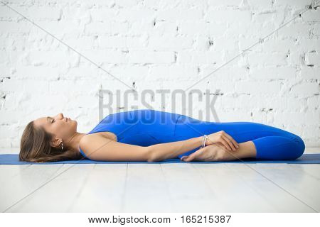 Young attractive woman practicing yoga, lying in Reclining Hero exercise, Supta Virasana pose, working out wearing sportswear, blue suit, indoor full length, white studio background