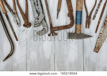 Old rusty tools lying on a painted board