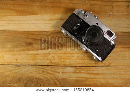 Retro photo camera on wooden the background