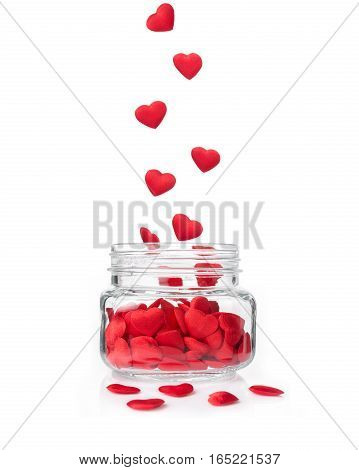 small red hearts falling in glass jar on white background concept for valentine or special occasion