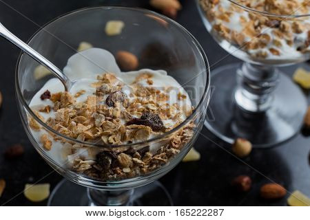 Granola With Yoghurt, Nuts And Fruits In Glass Bowl On Dark Background. Delicious, Healthy Sweet Des