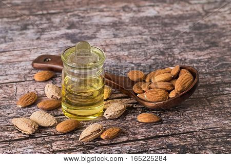 The almonds peeled and not peeled in a wooden spoon, nearby a small glass small bottle with almond oil.