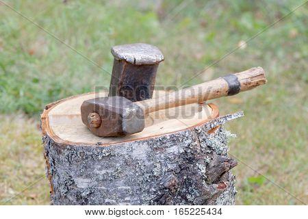 Sledgehammer and a wedge splitting a birch log