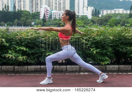 Side view of female athlete training doing lunge exercises with hands outstretched outdoors in city park