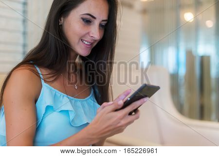 Young woman wearing casual clothes chatting on smart phone smiling looking relaxed and happy while sitting in a room with white furniture. European girl using apps on cellphone.